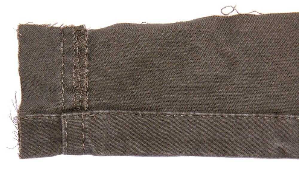 Twill textile showing seam allowance and tattered threads.