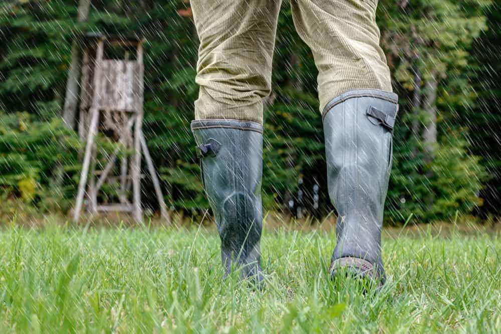 Hunter in green rubber boots walking through the rain.