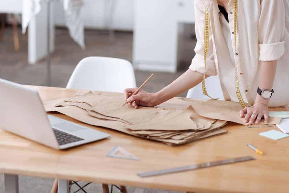 Woman writing on a dress pattern.