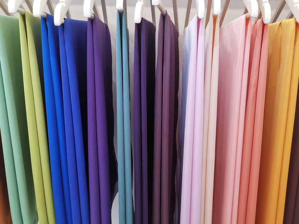Multicolored satin fabric on hangers.