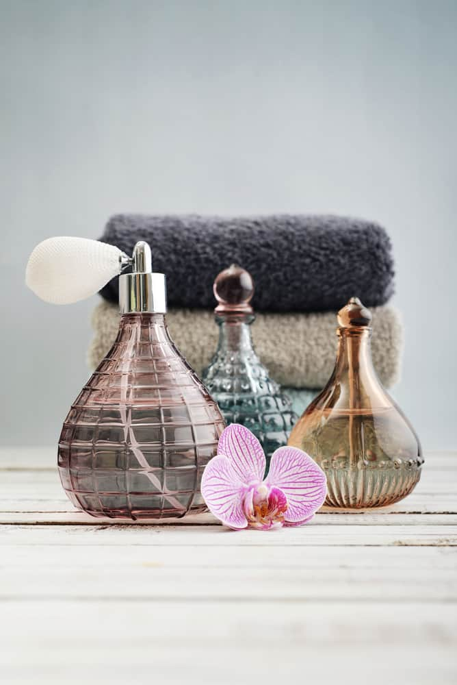 Perfume bottles and a pile of towels over a wooden surface.