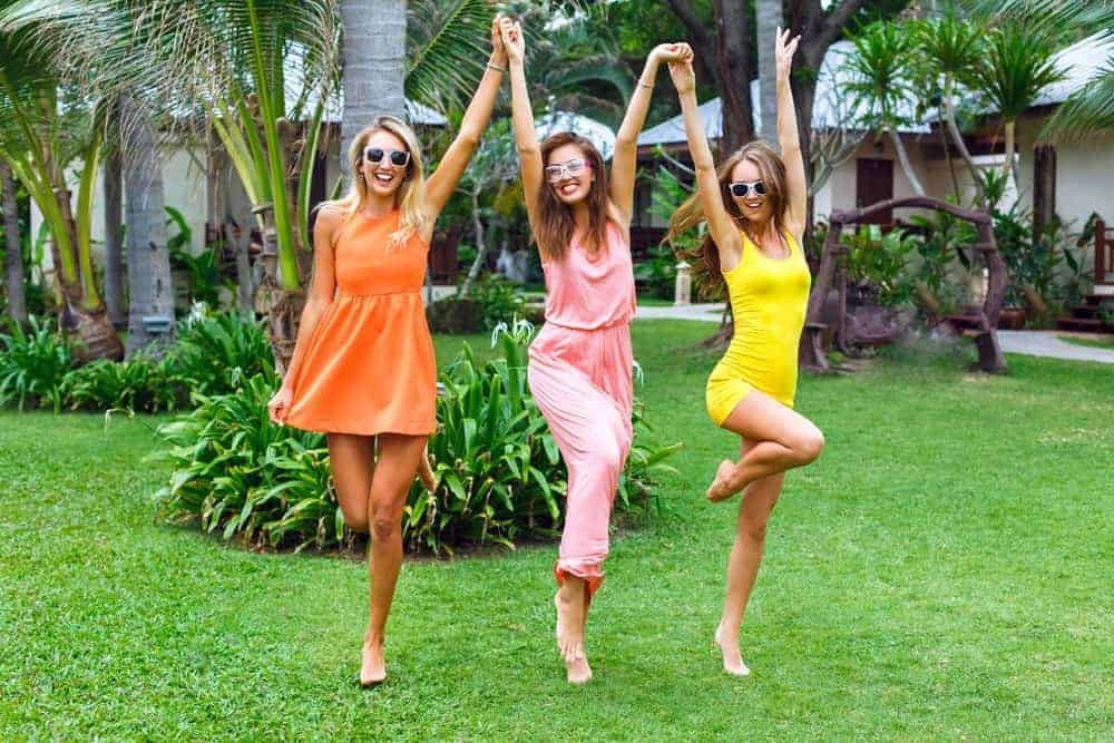Three women wearing colorful summer outfits at a beach resort.