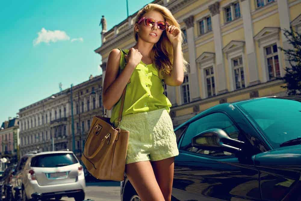A woman wearing a bright green summer ensemble while walking on the sidewalk.