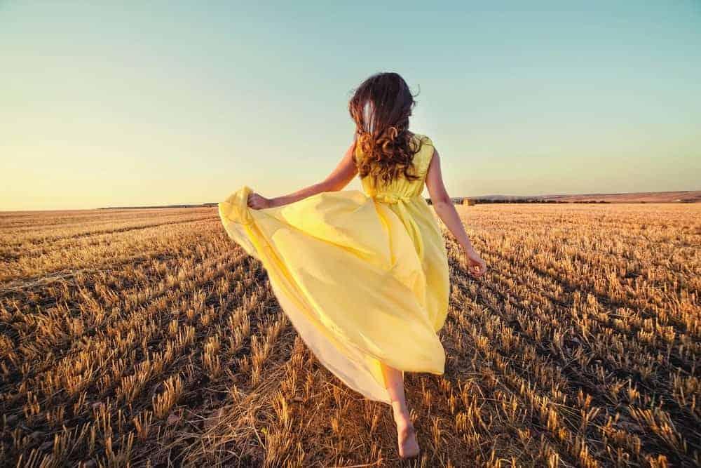 A woman running through the field wearing a buttercream yellow summer dress.