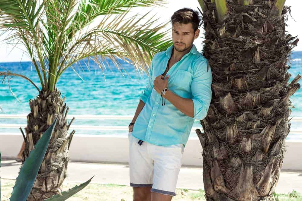 A man wearing a fashionable outfit of white shorts and blue button-down shirt at the beach.