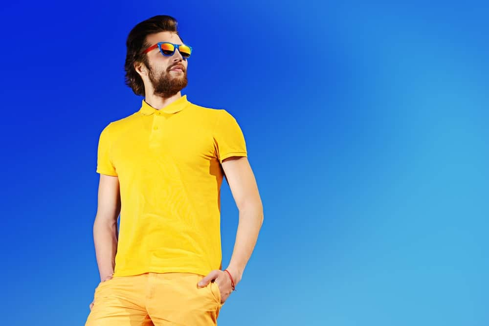 A man wearing a matching neon yellow shirt and shorts against a blue sky.