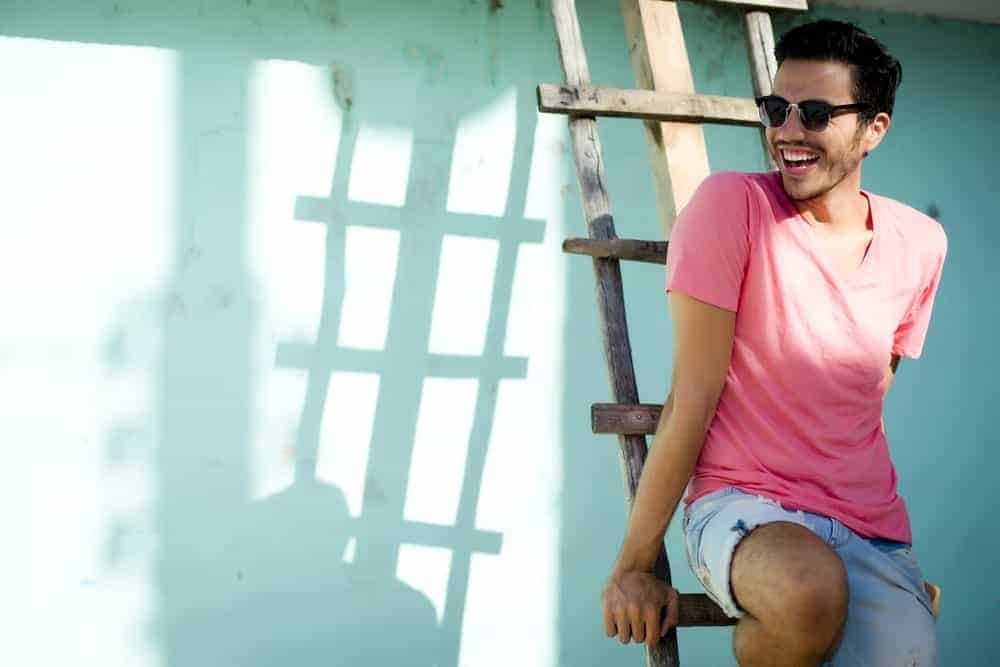 A man wearing a pair of sunglasses and a pastel pink shirt sitting on a wooden ladder.