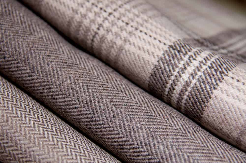 A pile of of neutral colored tweed wool fabrics.