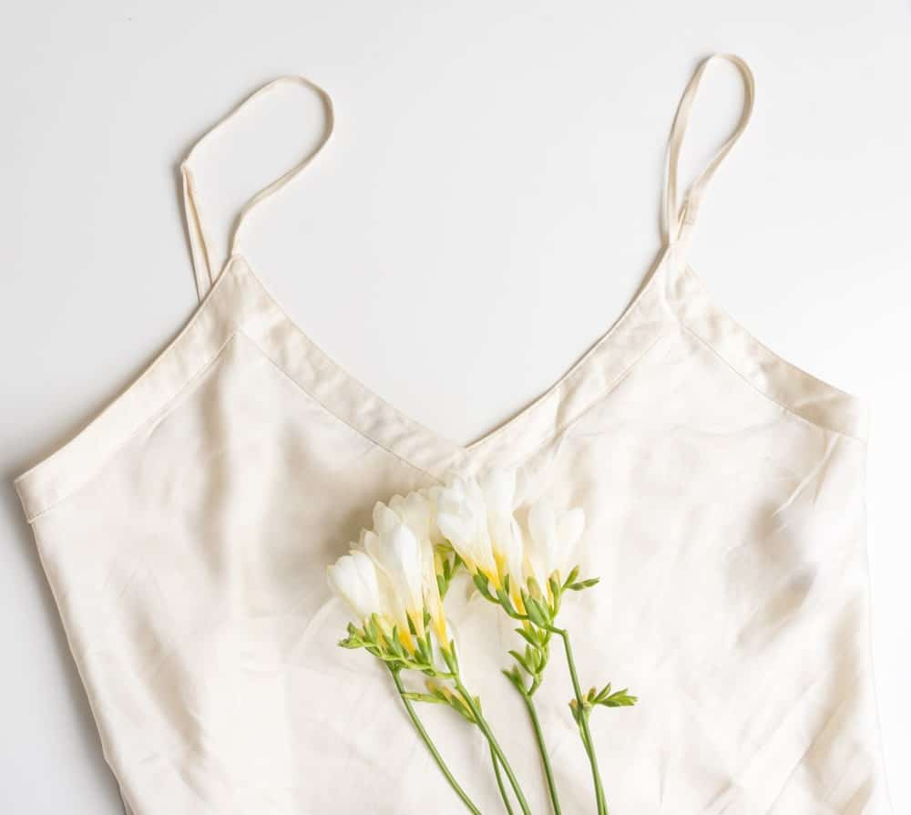A silky white camisole with a cluster of white flowers.