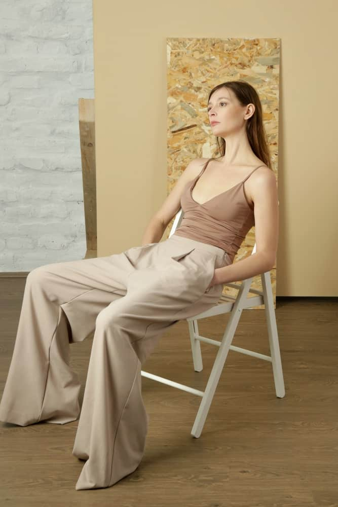 This is a close look at a woman wearing a pair of beige pants with her beige camisole.