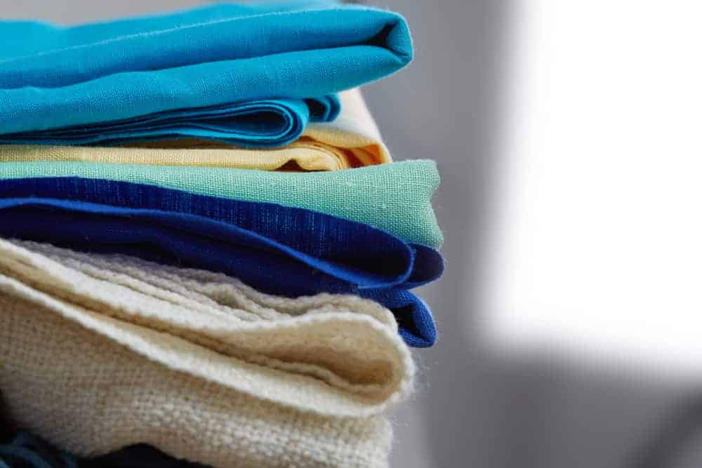 A pile of multicolored cloth fabrics with various textures.
