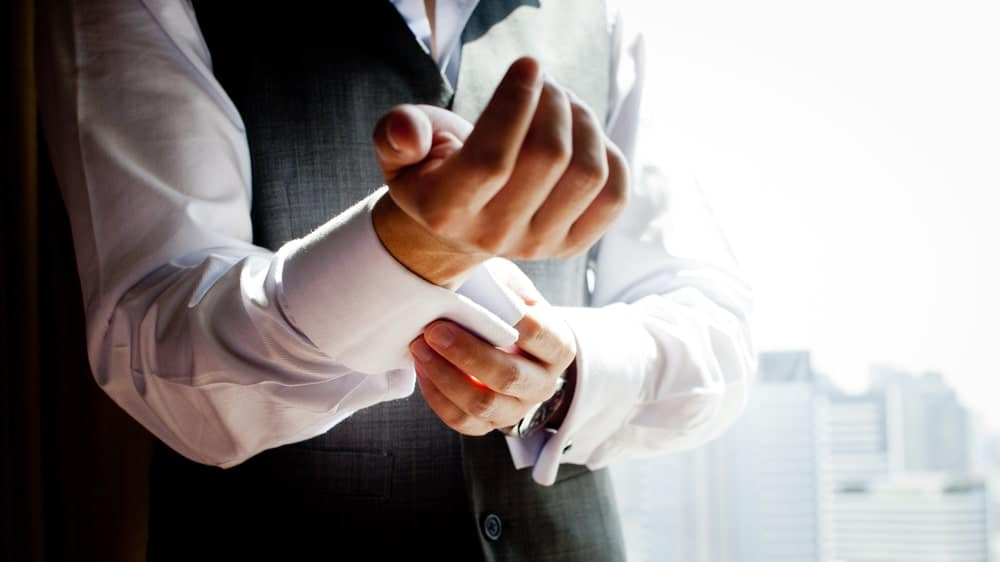 This si a close look at a man adjusting his cuffs.