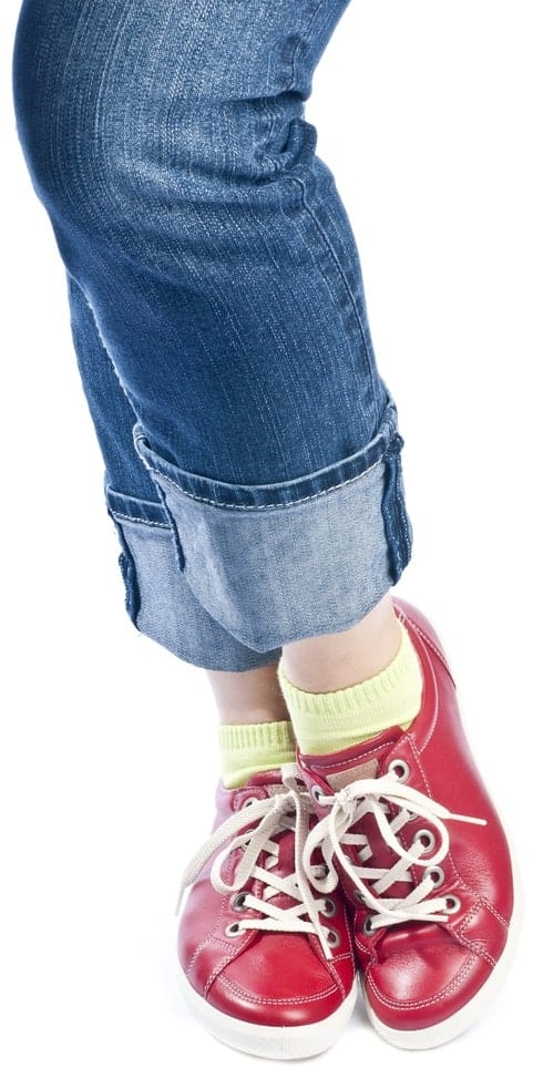 A close look at a woman with long cuffs on her jeans.