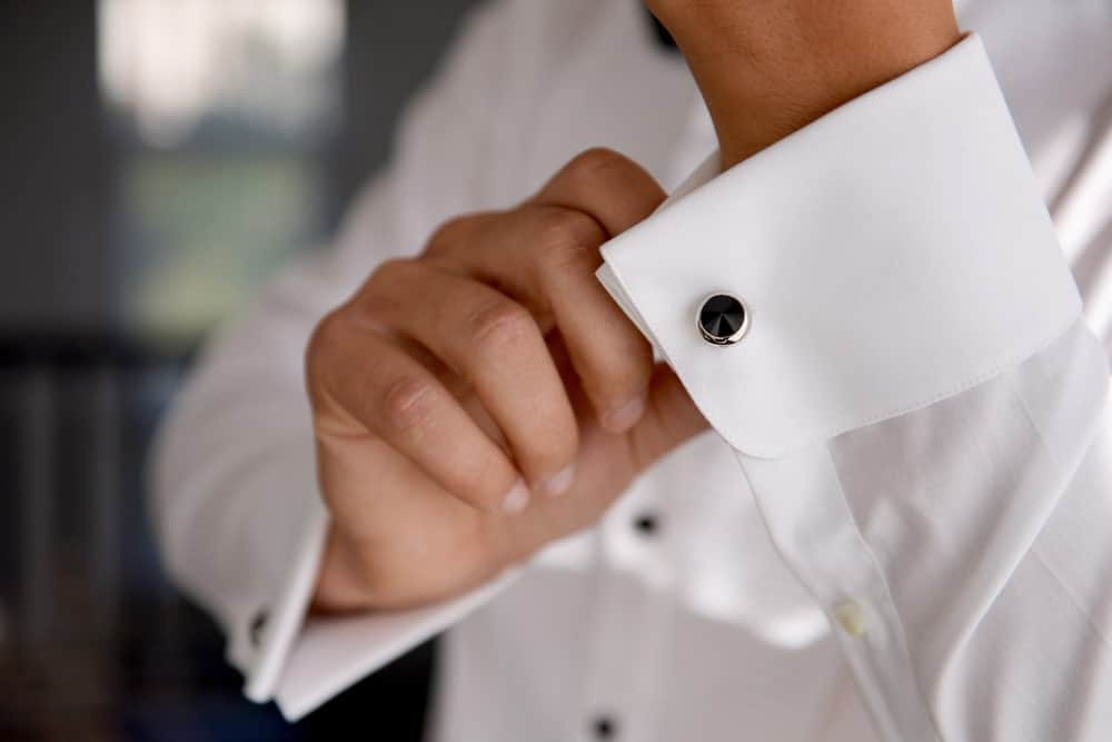 A close look at a man wearing cufflinks on his white cuff.