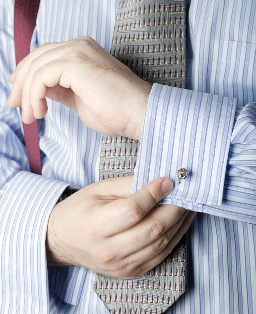 This is a close look at a man wearing a striped shirt with French cuffs.