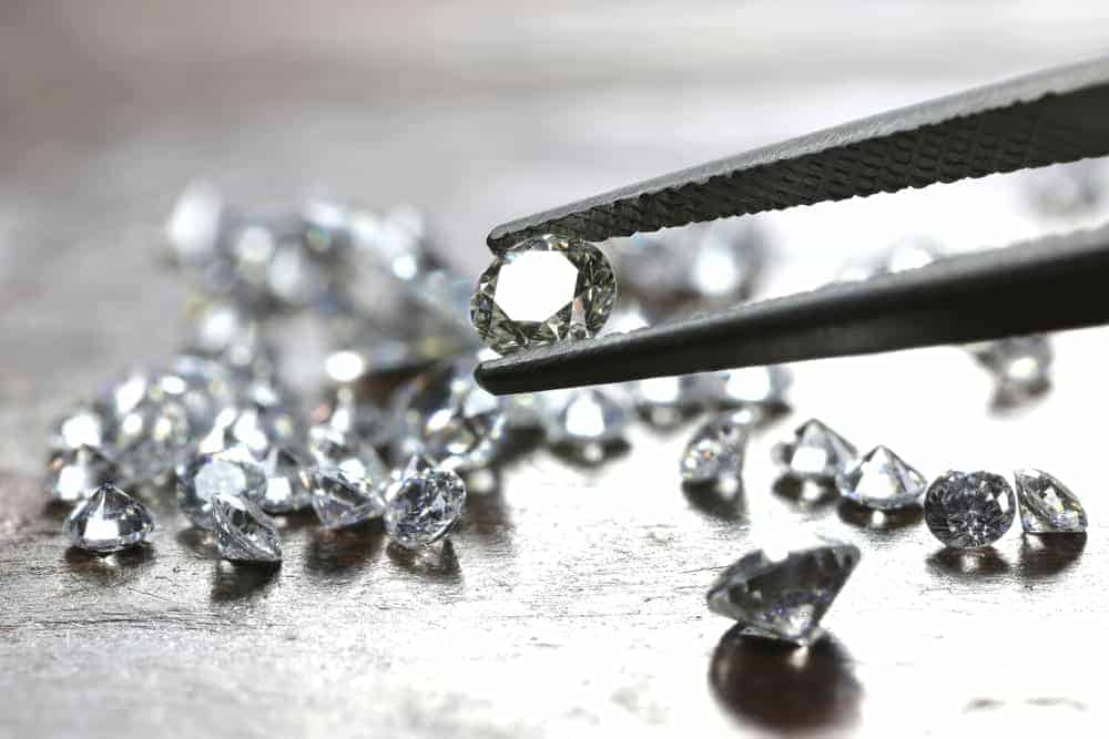 A close look at a pair of tweezers picking out one of the bunch of cut diamonds.