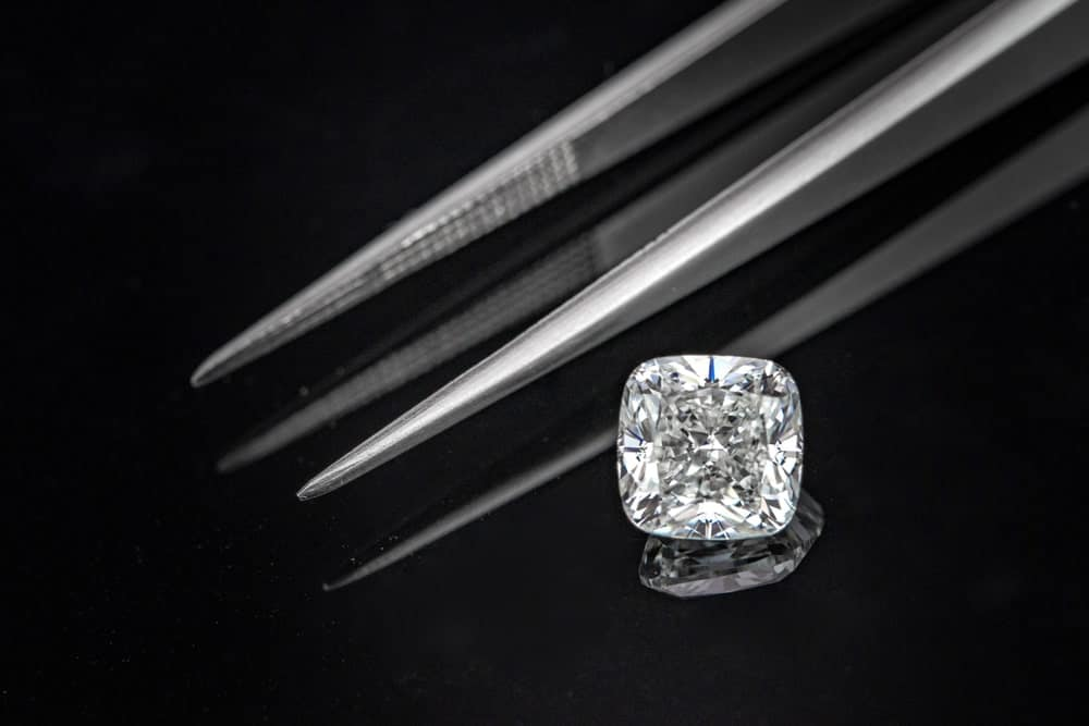 A cushion cut diamond stands out against the tweezers and dark surface.