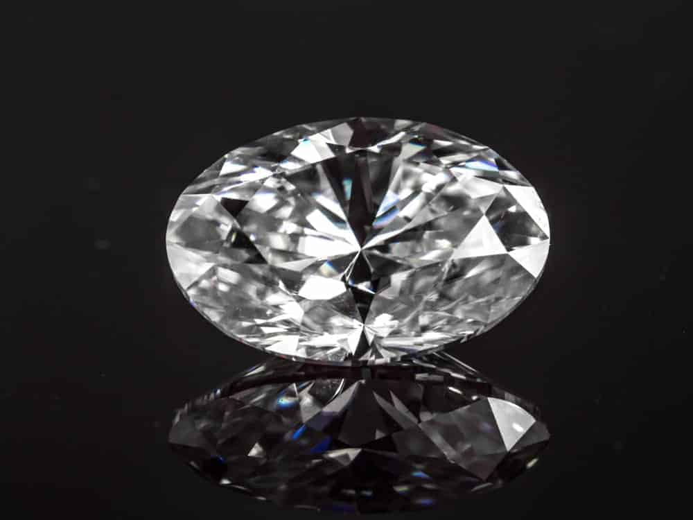 This is a close look a pice of oval cut diamond against a dark surface,