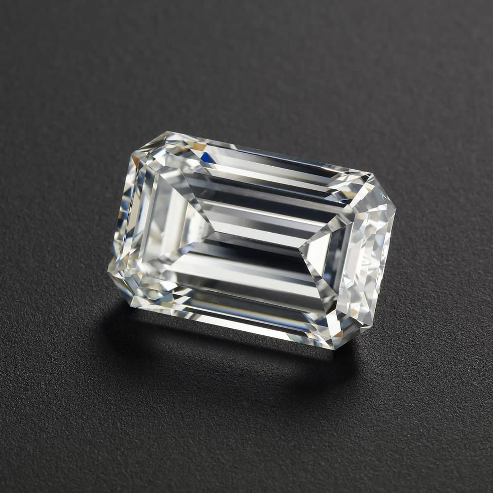 This is a close look at an emerald cut diamond on a dark surface.