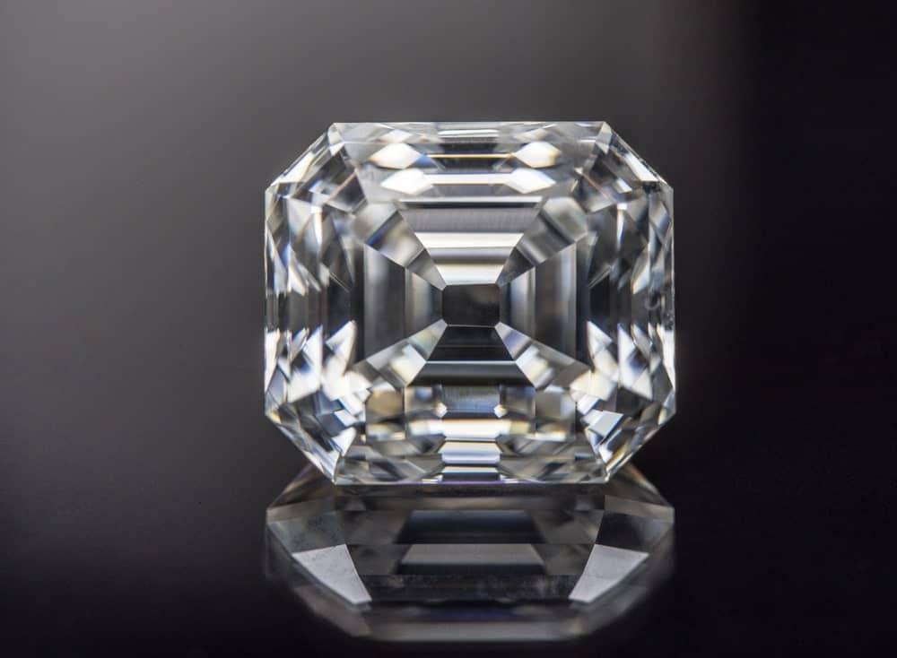 This is a close look at an Asscher cut diamond on a dark surface.