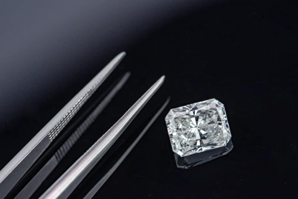 This is a close look at a radiant cut diamond on a dark surface with a pair of tweezers.