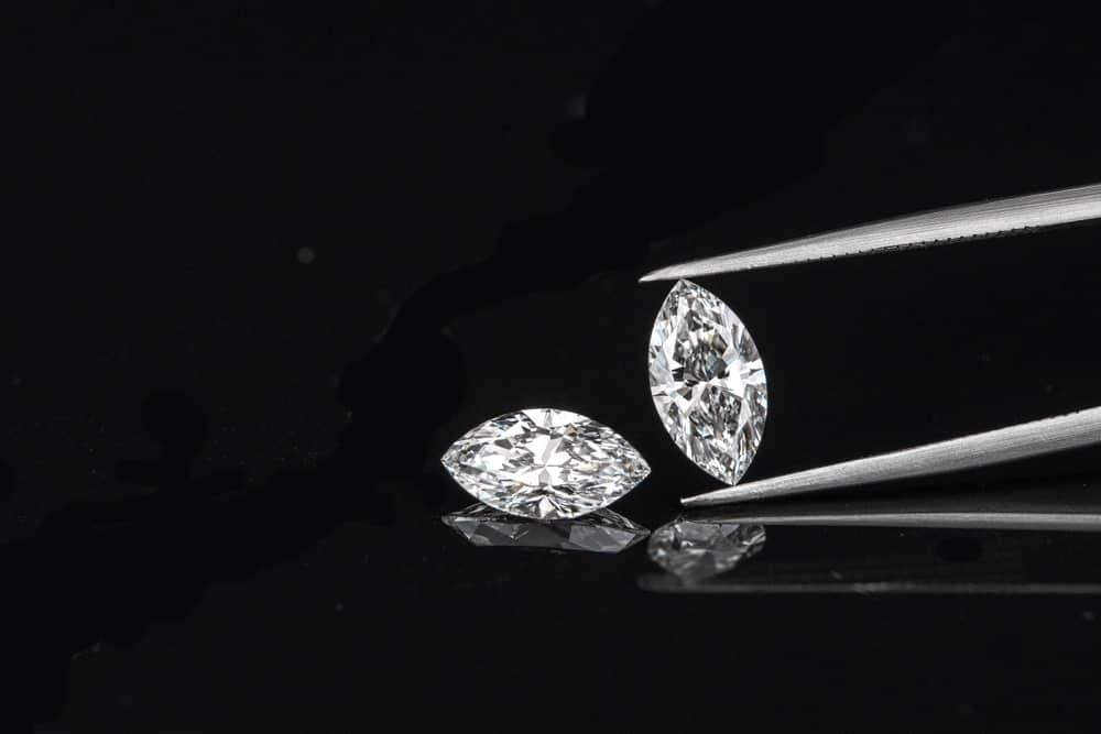 A pair of marquise cut diamonds against a dark surface with a pair of tweezers.