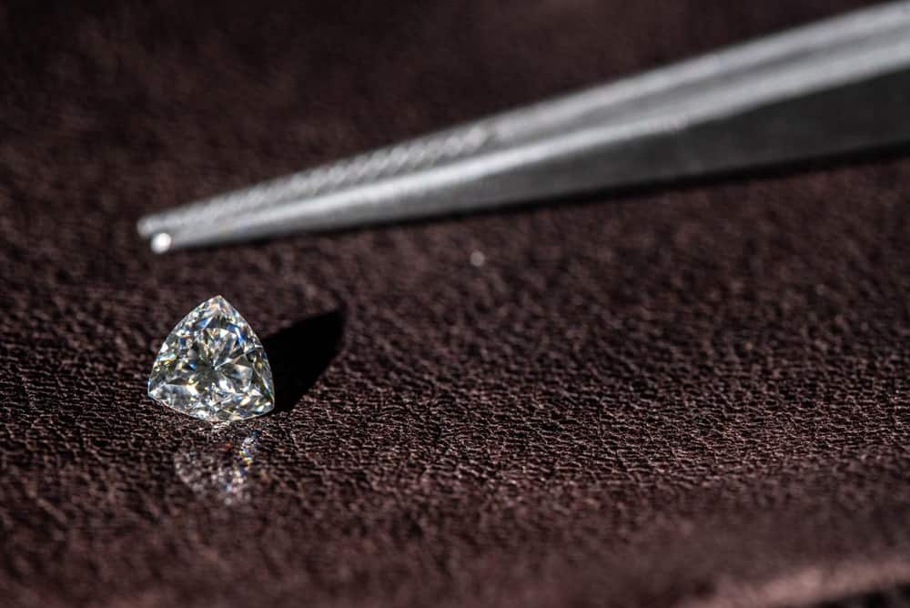 This is a close look at a single trillion cut diamond with a pair of tweezers.