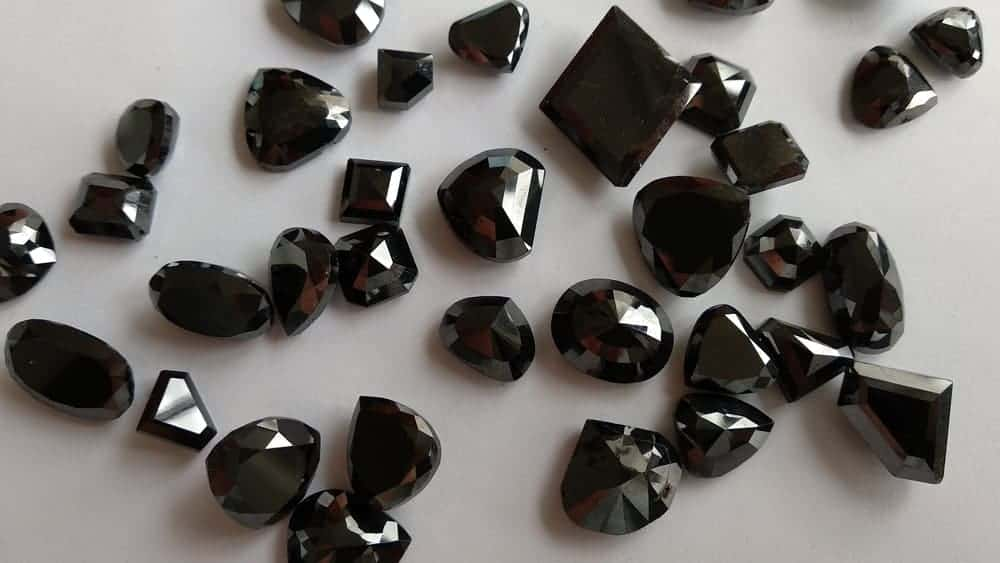 A look at a bunch of treated black polished diamonds.