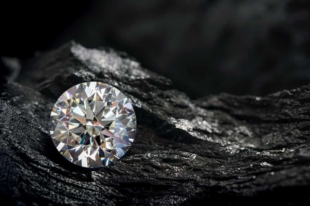A close look at a round cut diamond against a black coal background.