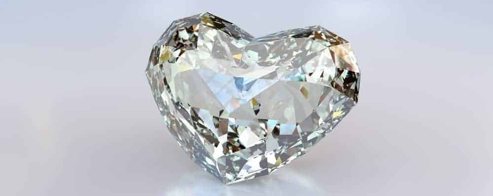 A close look at a heart-shaped diamond on a white surface.
