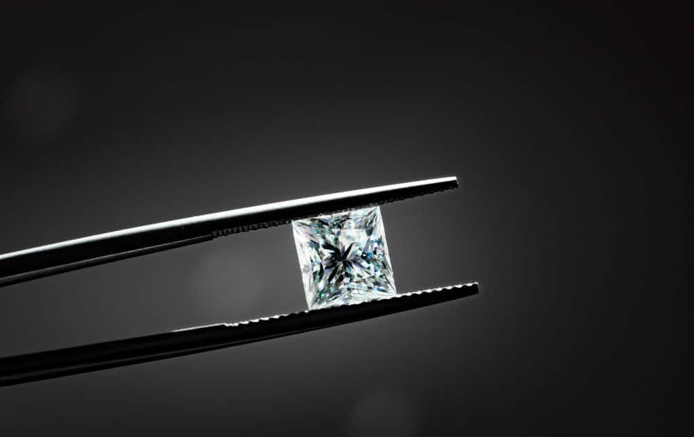 This is a close look at a princess cut diamond held with a pair of tweezers.