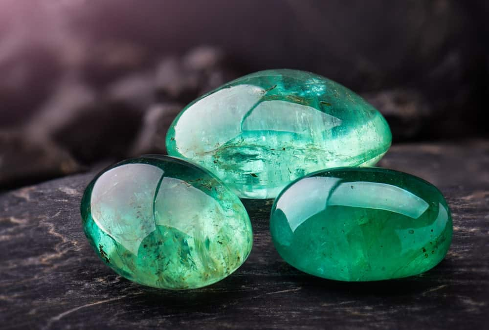 This is a close look at a few emeralds on a dark surface.