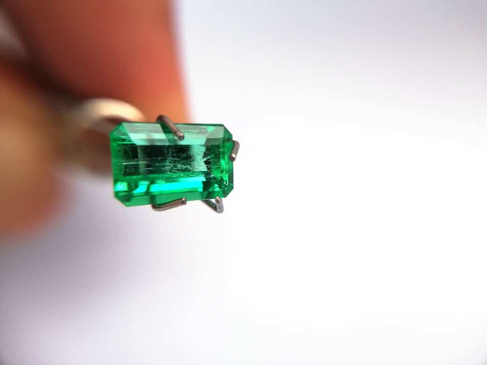 This is a close look at a Columbian emerald held with a pair of tweezers.