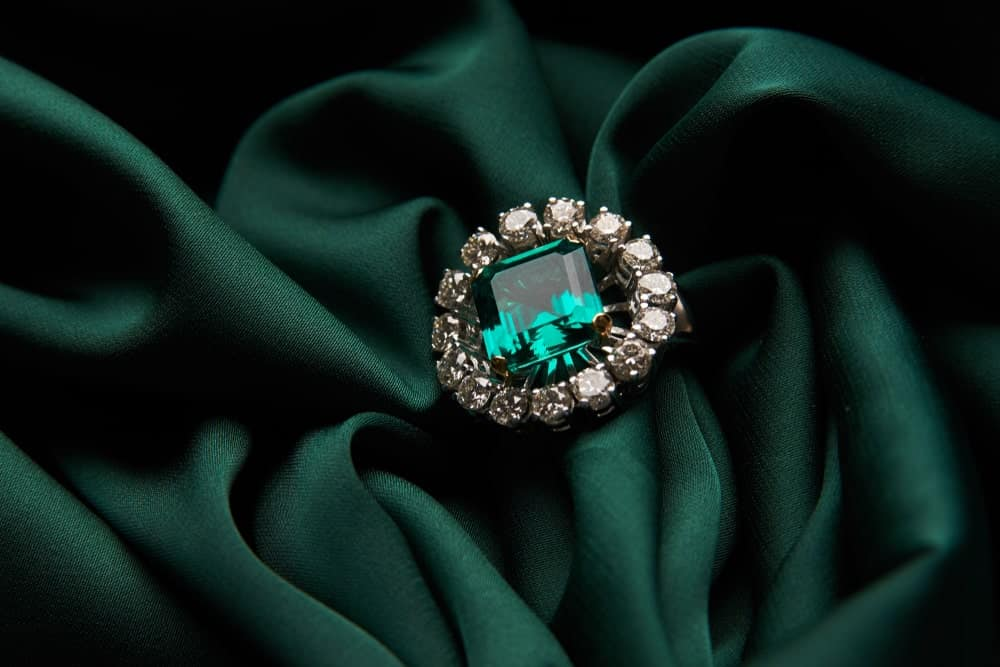 This is a close look at a ring with a large emerald surrounded by diamonds.