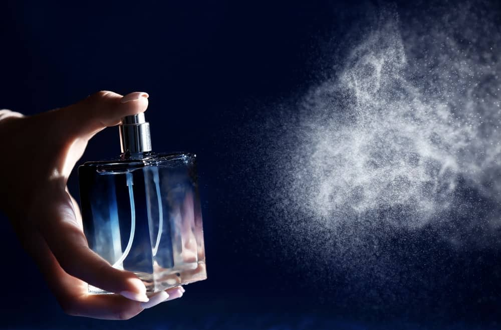 This is a close look at a woman spraying perfume.