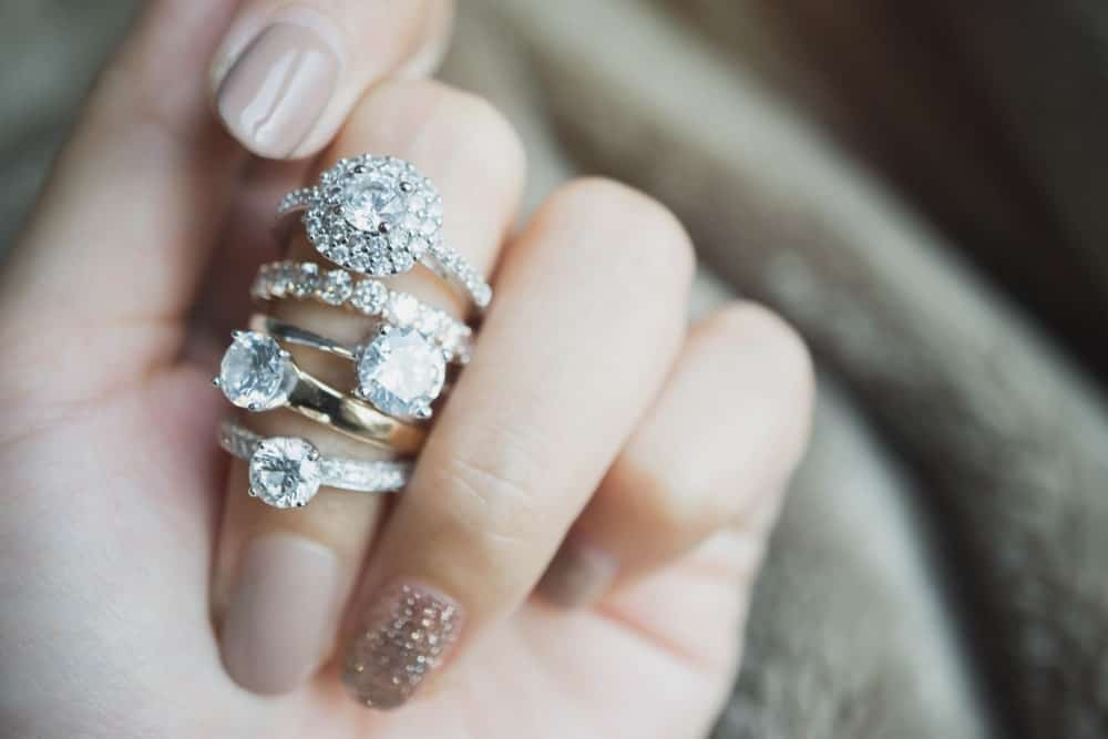 A woman wearing a variety of diamond rings on her finger.