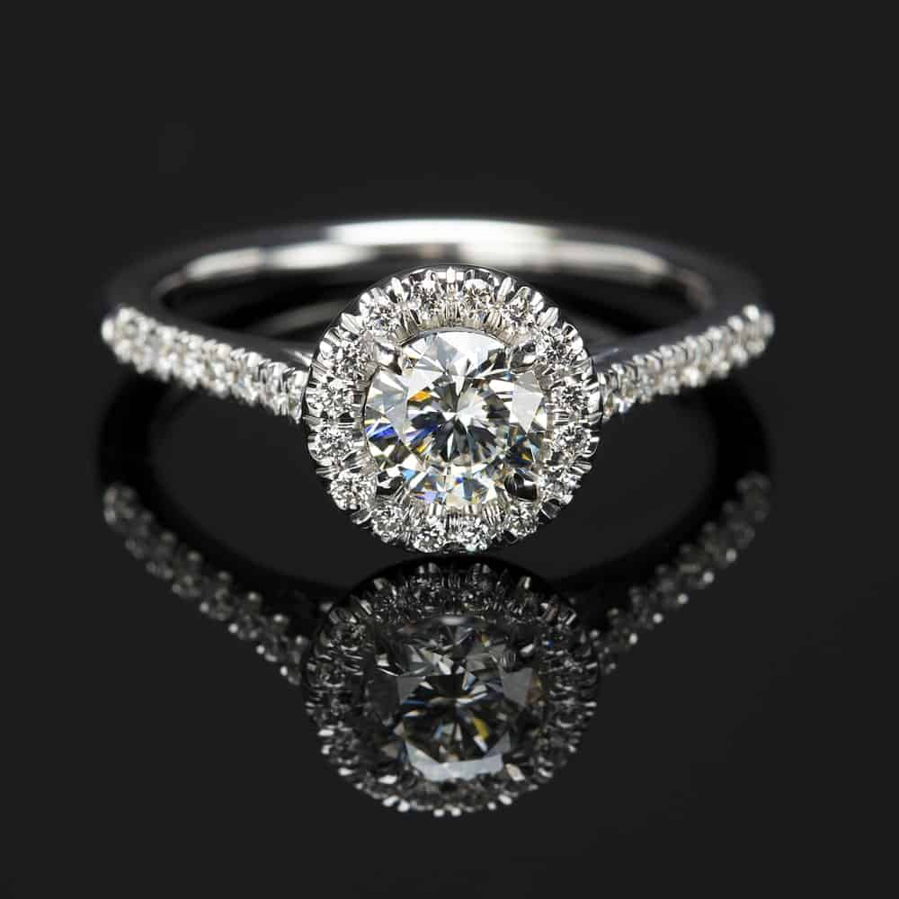 This is a close look at a halo diamond ring on a dark reflective surface.