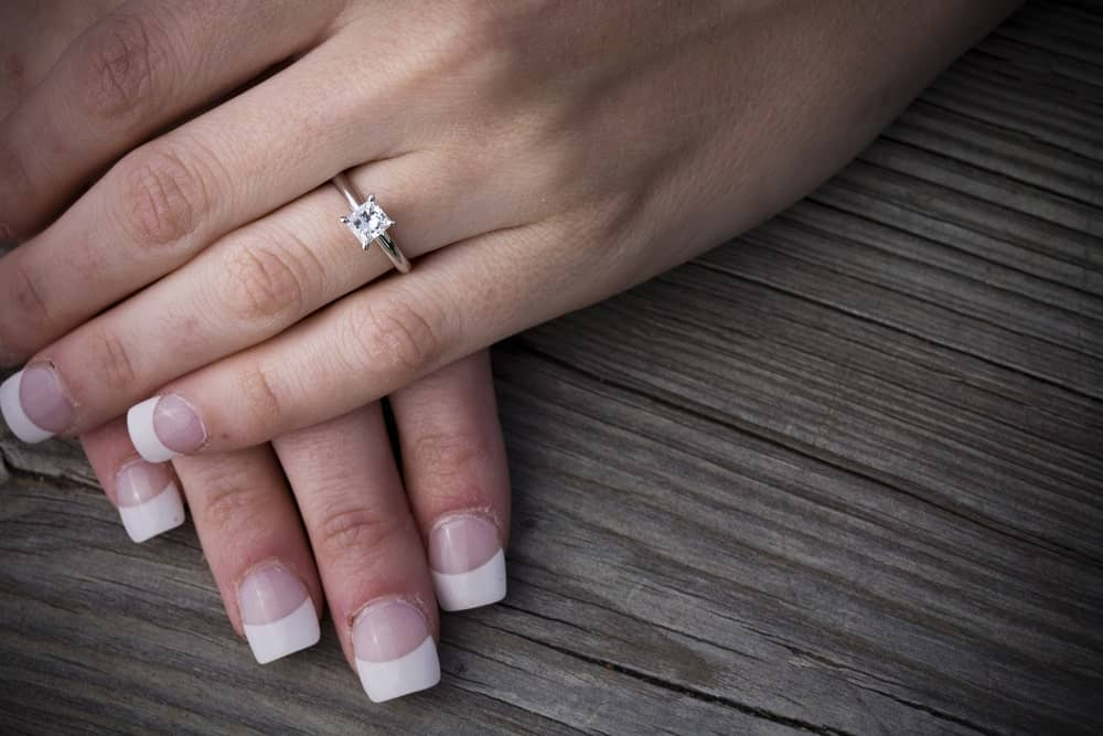 This is a close look at a woman's hands wearing a princess cut ring.
