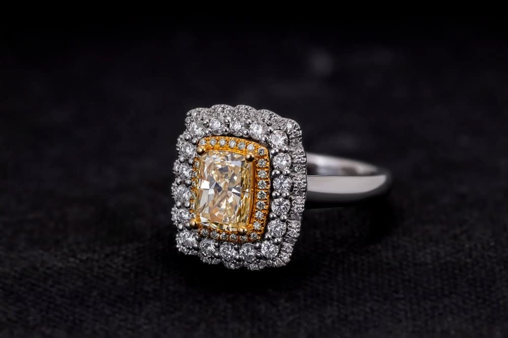 This is a cushion cut ring with diamonds on a dark surface.