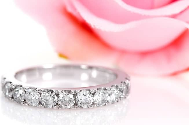 This is a close look at an eternity band with diamonds on a white surface.