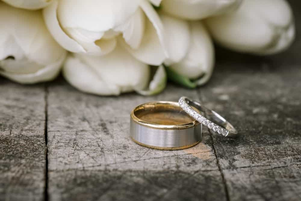 This is a close look at a couple of wedding bands with white roses.