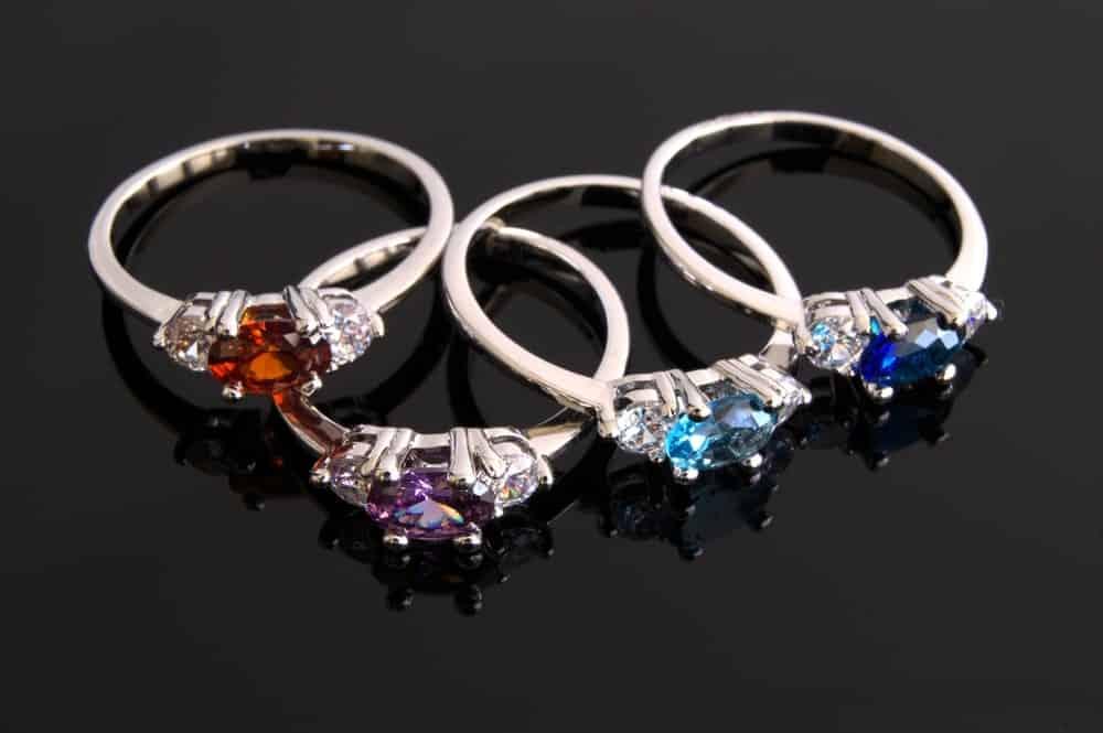 Various birthstone rings on a dark surface.