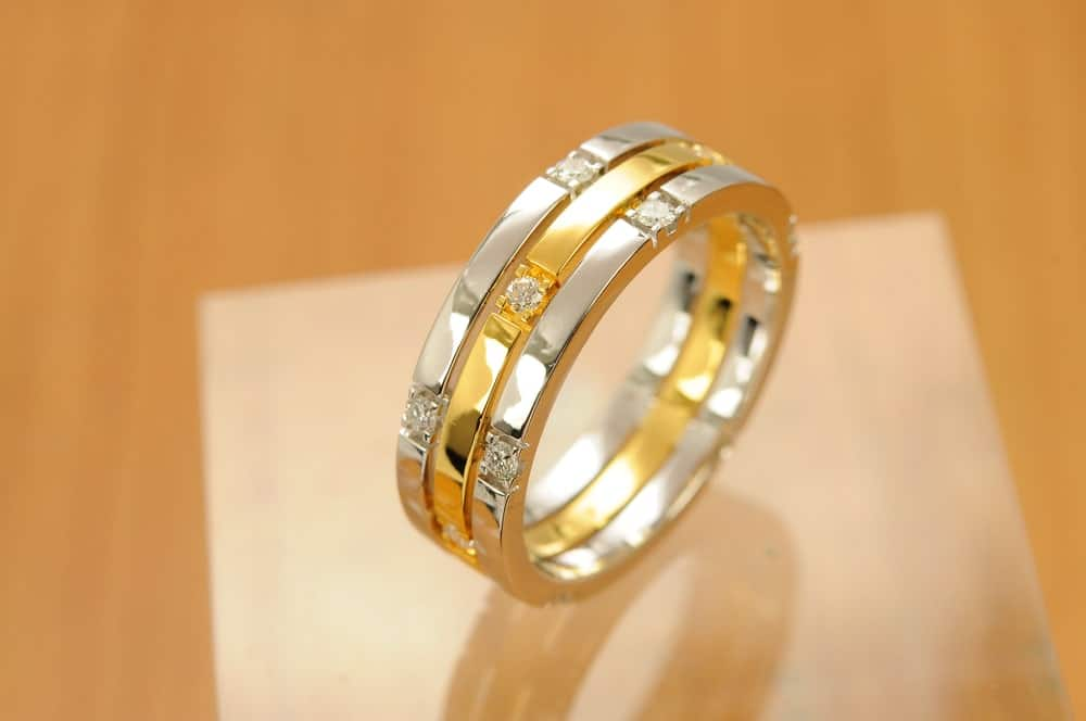 A two-tone band ring with diamonds on a wooden surface.