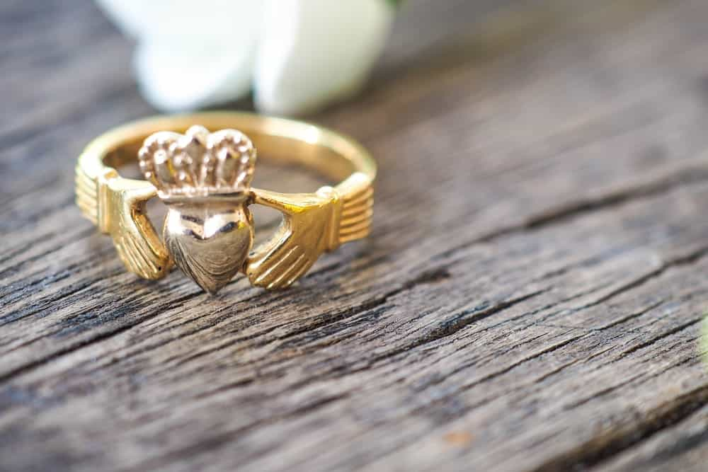 This is a close look at a Claddagh Ring on a wooden table.