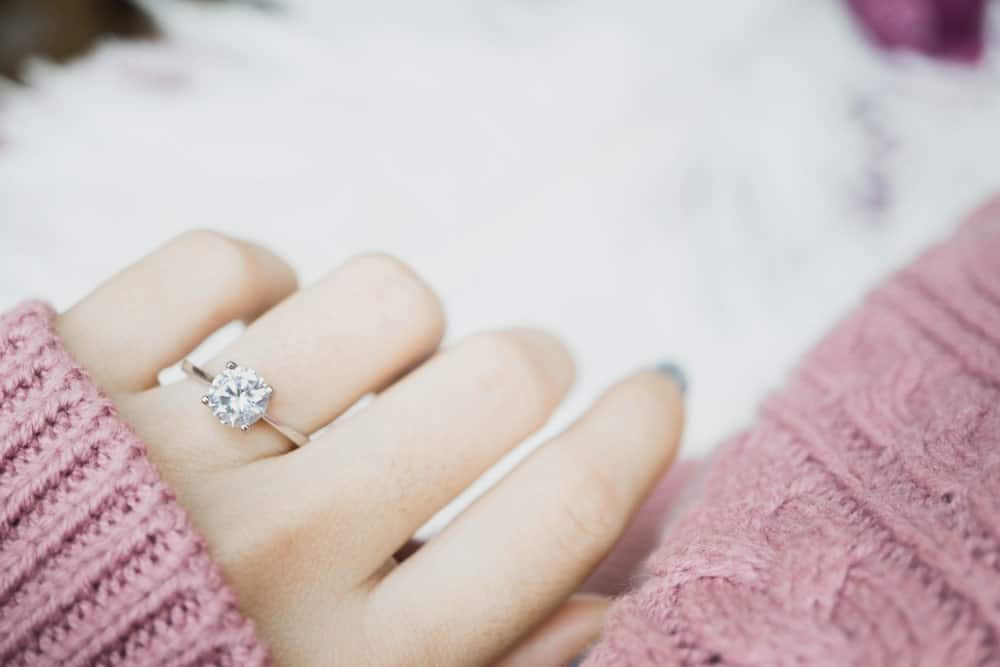 This is a close look at a woman's hand wearing an engagement ring.