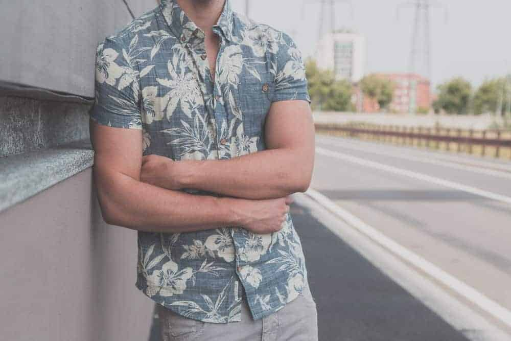 This is a close look at a man wearing a button-down Hawaiian shirt that has short sleeves.