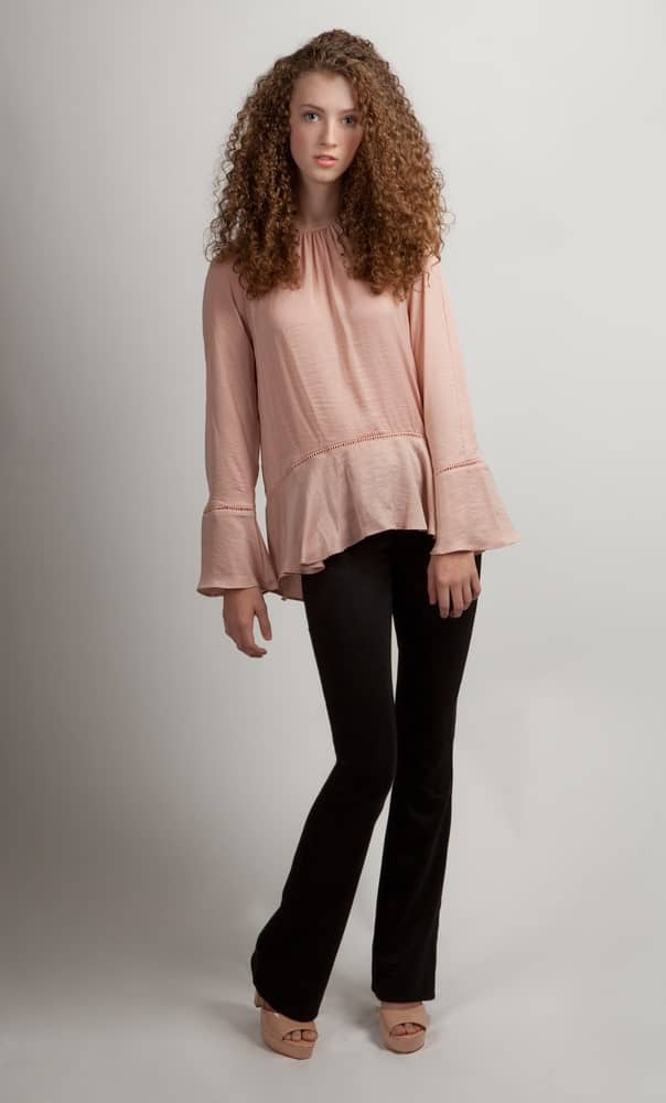 This is a woman wearing a pink shirt with long bell sleeves.