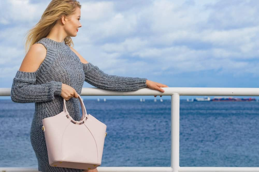 A woman at the ferry wearing a gray fleece dress with cold shoulder sleeves.