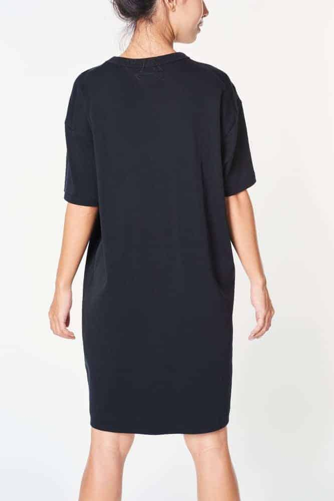 A close look at the back of a woman wearing a black dress with drop shoulder sleeves.