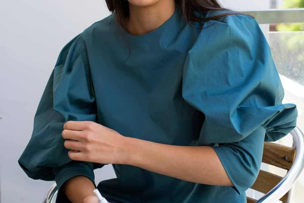 A woman wearing a teal blouse that has puff sleeves.